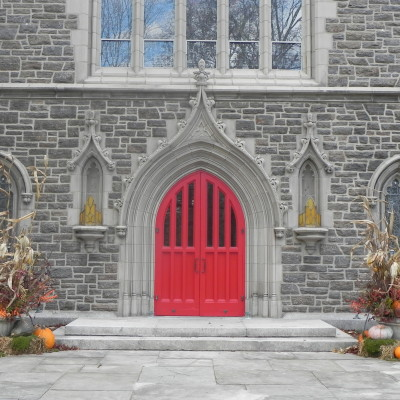 The main entrance to the church (sanctuary) is just through these red doors. The main parking lot is located just east (left) of this building.