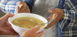 Hands-passing-bowl-of-soup